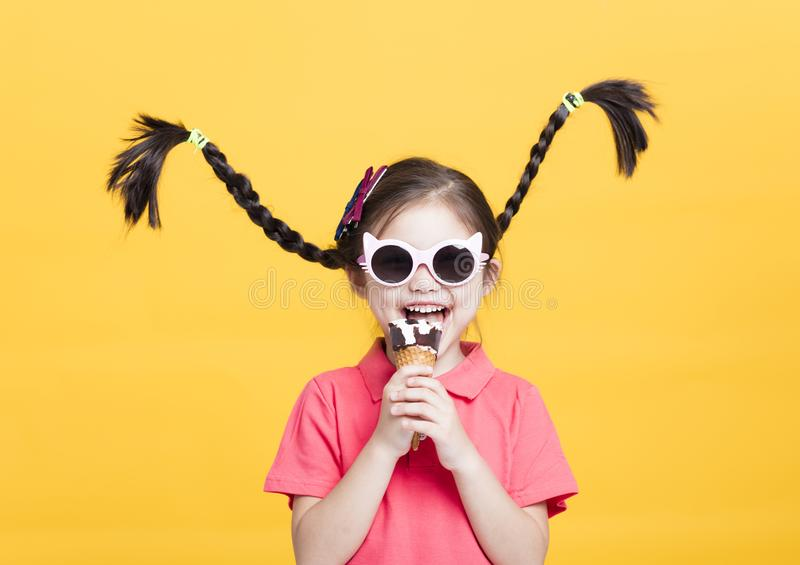 Smiling little girl eating ice cream royalty free stock photo