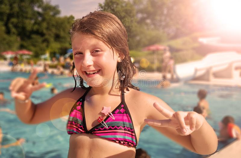 Smiling little girl is enjoying in the pool in a summer day stock photos