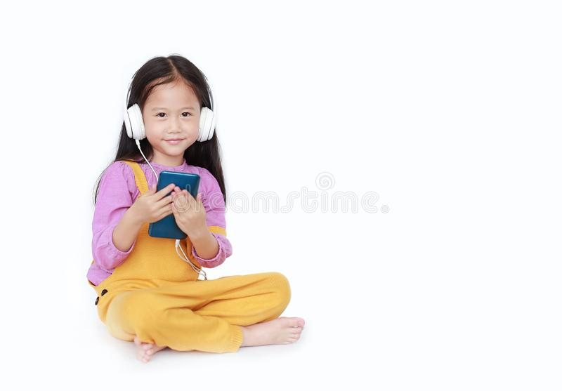 Smiling little girl enjoys listening to music by headphones isolated over white background with copy space.  royalty free stock photo