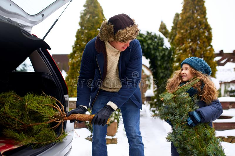 Smiling little girl and father get christmas tree out of car trunk near their house outdoors. Daughter helps dad with royalty free stock image