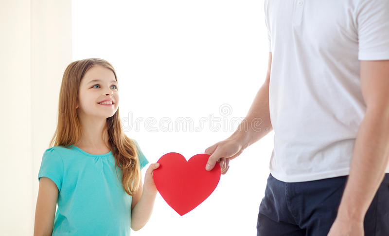 Smiling little girl and father holding red heart. Family child, health, charity and love concept - smiling little girl and father holding red heart stock photo