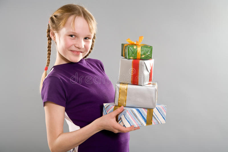 Smiling little girl with gift boxes stock photo