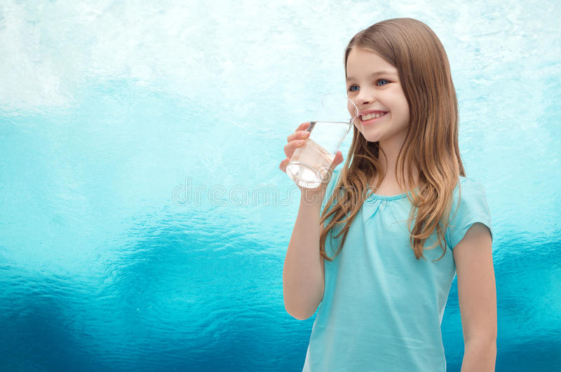 Smiling little girl with glass of water royalty free stock photography