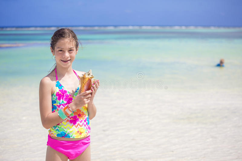 Smiling little girl holding a seashell on a scenic beach royalty free stock image