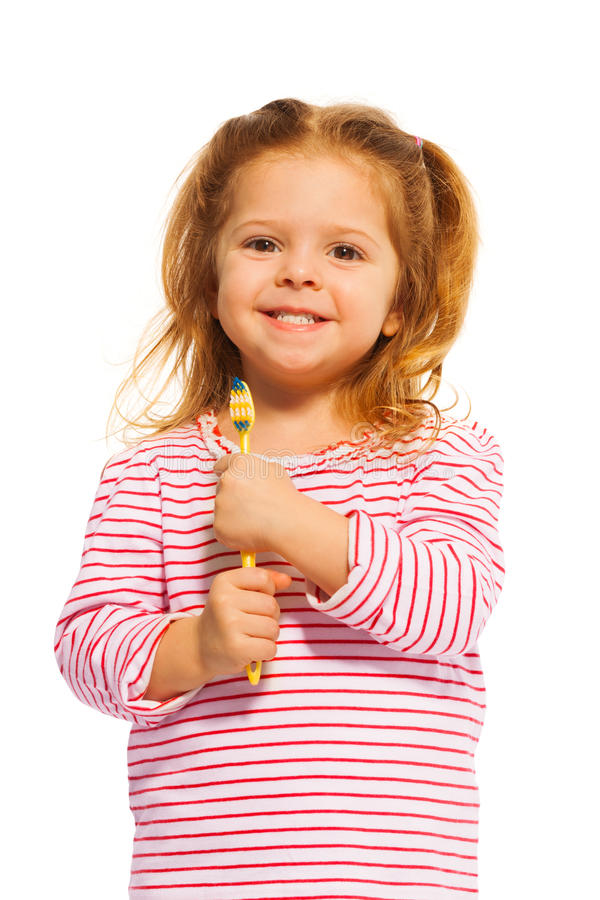 Smiling little girl holding yellow toothbrush royalty free stock photo