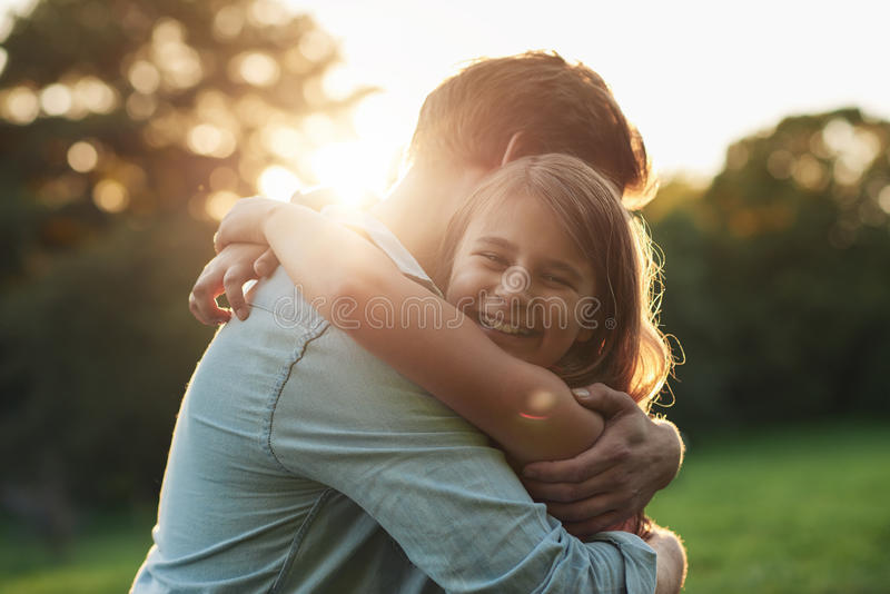 Smiling little girl hugging her father outside. Portrait of a smiling little girl affectionately hugging her father while enjoying a day together in a park on a royalty free stock image