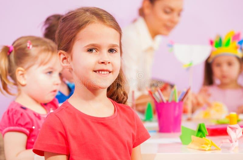 Smiling little girl in kindergarten classroom stock images