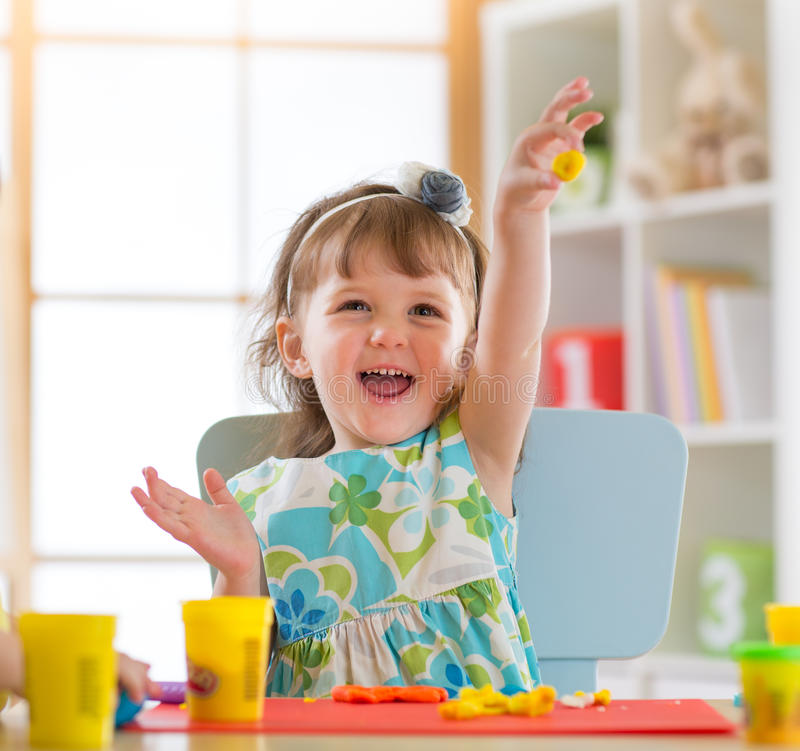 Smiling little girl is learning to use colorful play dough in a well lit room near window stock images