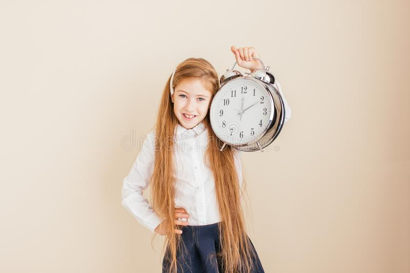 Smiling little girl with long hair holding big clock on neutral background. Time management, deadline, time to study, school. Concept stock photography