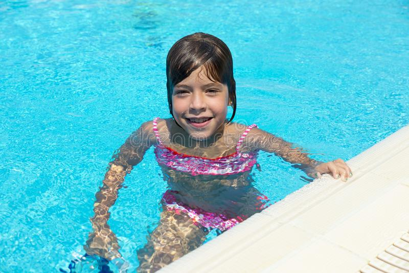 Smiling little girl looking at camera in an outdoor pool stock photo
