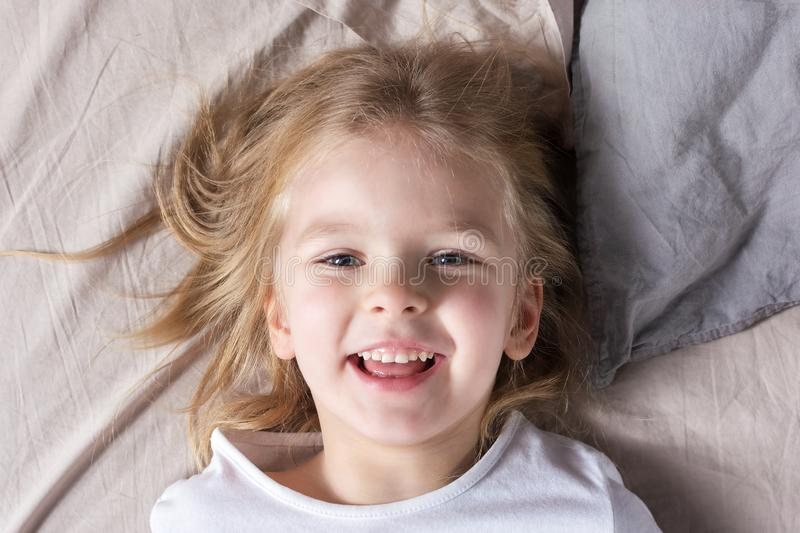 Smiling little girl is lying on the bed. A child with beautiful eyes and bright emotions. stock photography