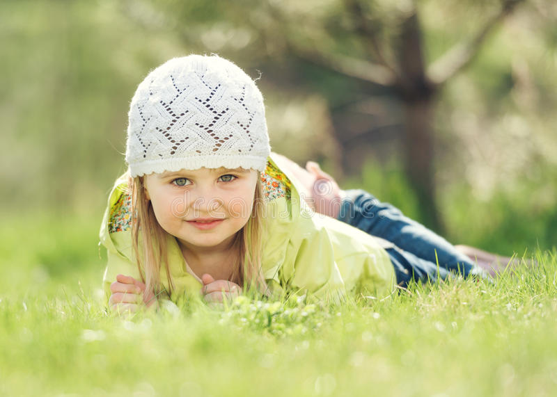 Smiling little girl lying on a lawn in the park stock photos