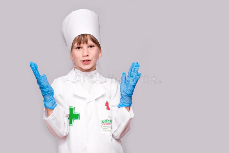 Smiling girl in medical uniform and blue gloves looking at camera isolated on white. Smiling little girl in medical uniform and blue gloves looking at camera royalty free stock image
