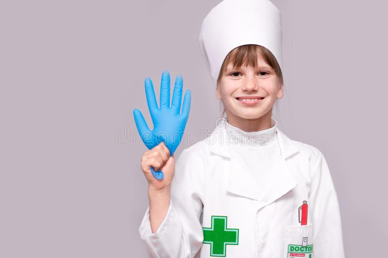 Smiling girl in medical uniform and blue gloves looking at camera isolated on white. Smiling little girl in medical uniform and blue gloves looking at camera stock photo