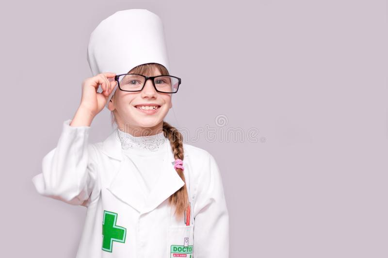 Smiling girl in medical uniform and glasses looking at camera isolated on white. Smiling little girl in medical uniform and glasses looking at camera isolated on stock photo