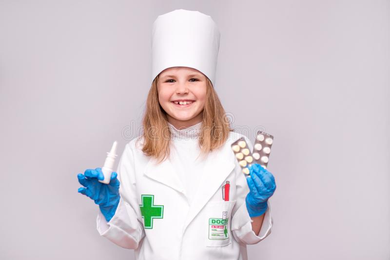 Smiling little girl in medical uniform holding nasal spray and pills for health. Doctor recommends medicine nose spray stock photo