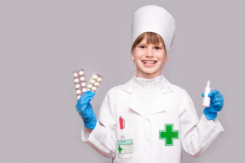 Smiling girl in medical uniform holding nasal spray and pills for health. Doctor girl recommends medicine nose spray. Smiling little girl in medical uniform stock photos