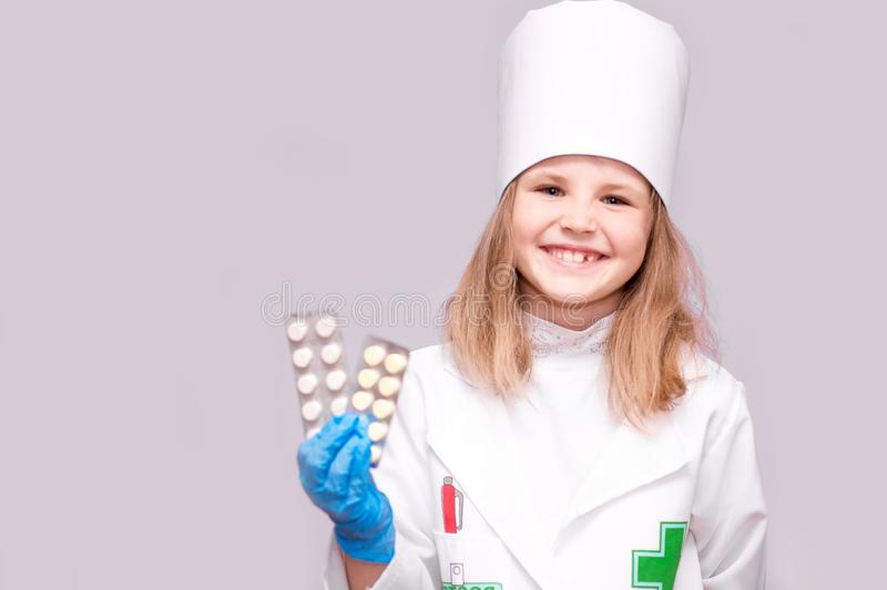 Smiling little girl in medical uniform holding pills for health. Doctor recommends medicine pills. Smiling little girl in medical uniform holding pills for royalty free stock photos
