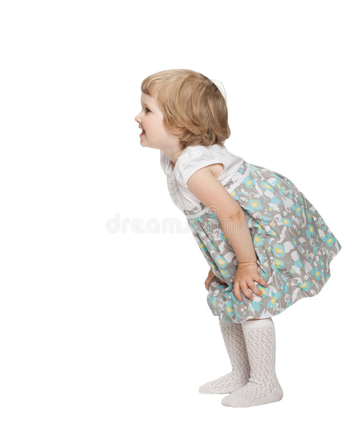 Smiling little girl playing. Smiling little girl bending and waiting something; neutral background royalty free stock photography
