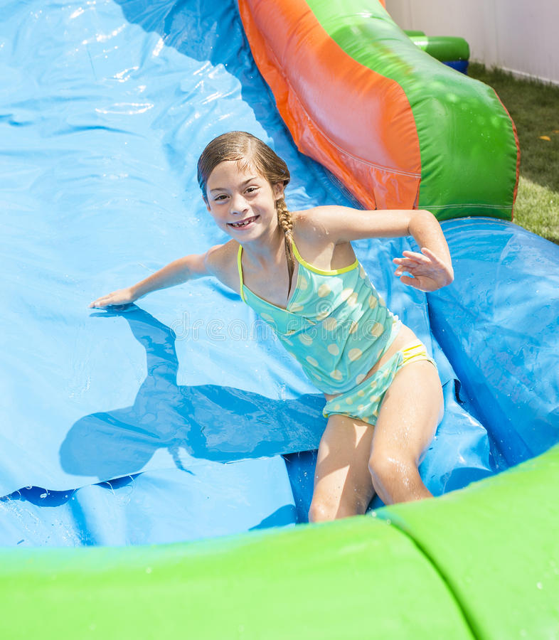 Smiling little girl playing on an inflatable slide bounce house. In her backyard outdoors on a sunny day royalty free stock image