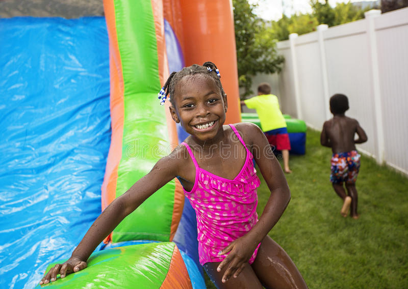 Smiling little girl playing outdoors on an inflatable bounce house. Cute smiling little African American girl playing on an inflatable bounce house outdoors royalty free stock images