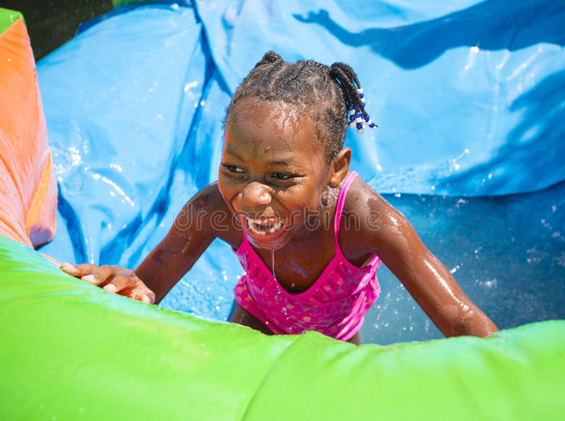Smiling little girl playing outdoors on an inflatable bounce house water slide. Cute smiling little African American girl playing on an inflatable bounce house stock photography
