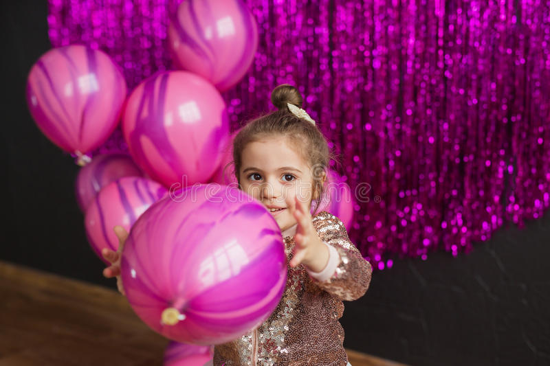 Smiling little girl plays with pink balloons and looks away. Smiling little girl plays with balloons and looks away stock photos