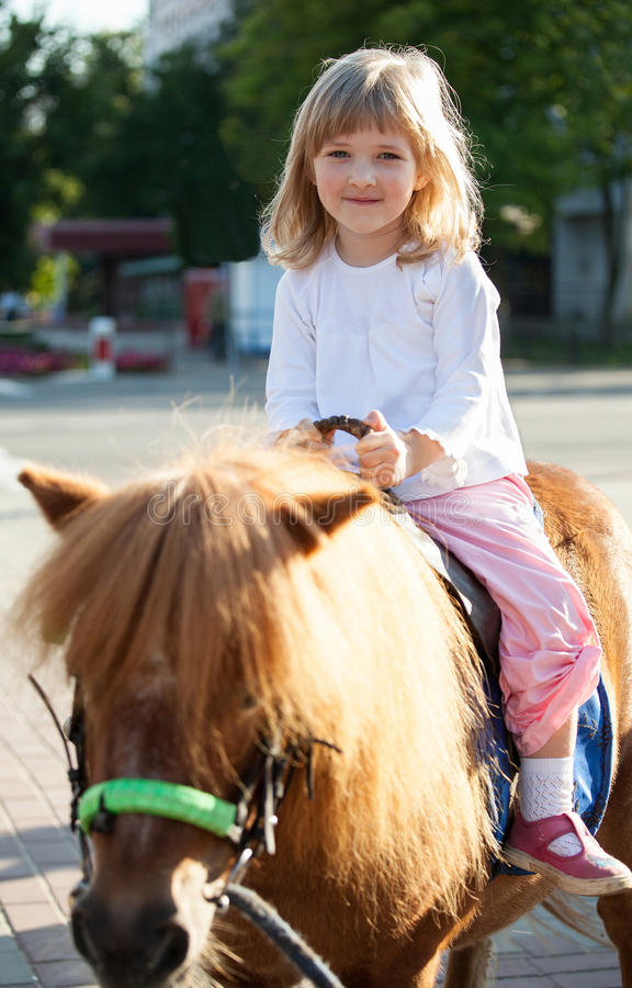 Smiling little girl on a pony royalty free stock photo
