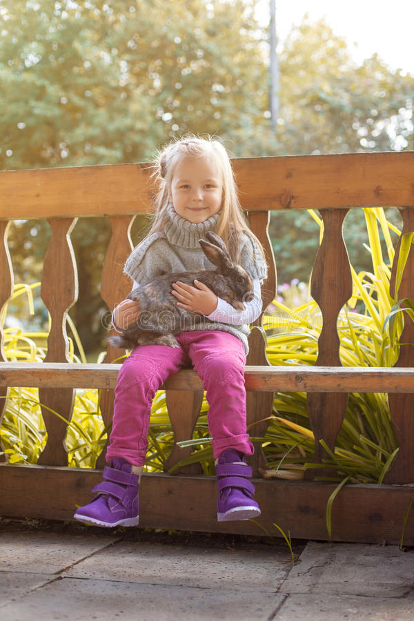 Smiling little girl posing in arbor with rabbit stock photo