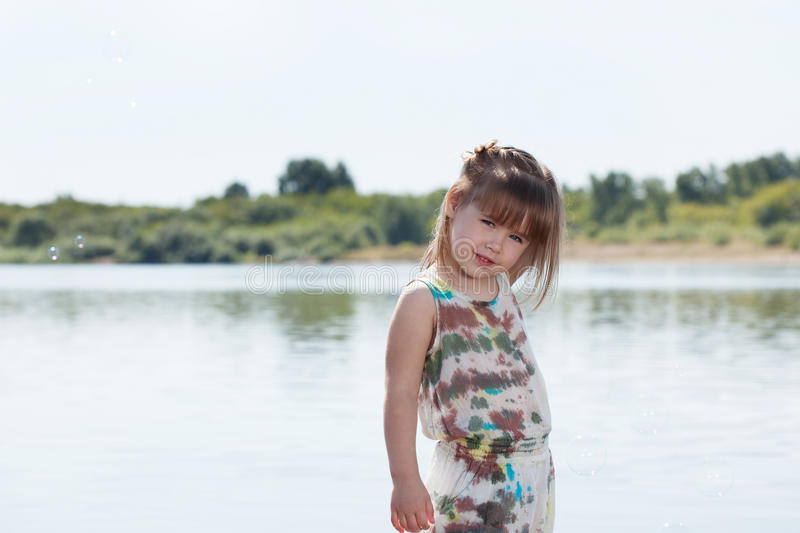 Smiling little girl posing by river stock images