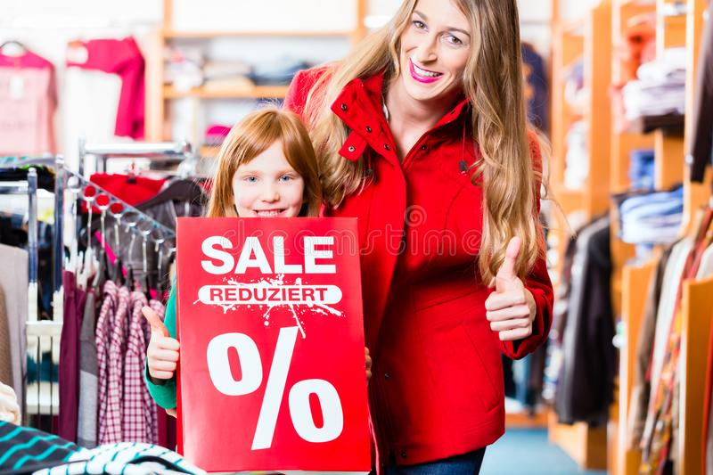 Little girl promoting sale offer in shopping mall stock images