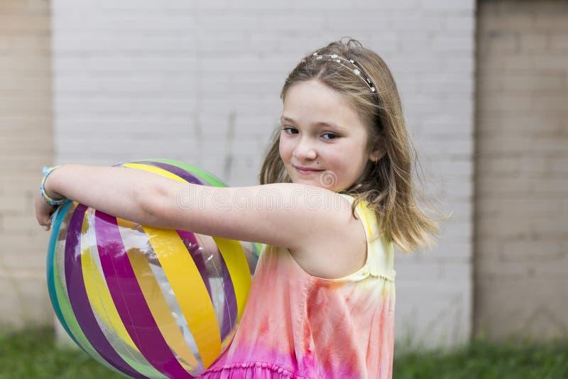 Smiling little girl in rainbow coloured dress holding a beach ball. Smiling little girl in rainbow coloured dress and blue string bracelet holding a beach ball stock photos