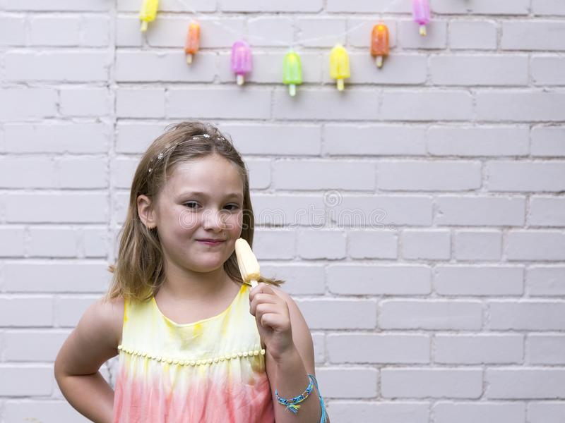 Smiling little girl in rainbow coloured dress holding a popsicle,. Smiling little girl in rainbow coloured dress and blue string bracelet holding a popsicle stock photos
