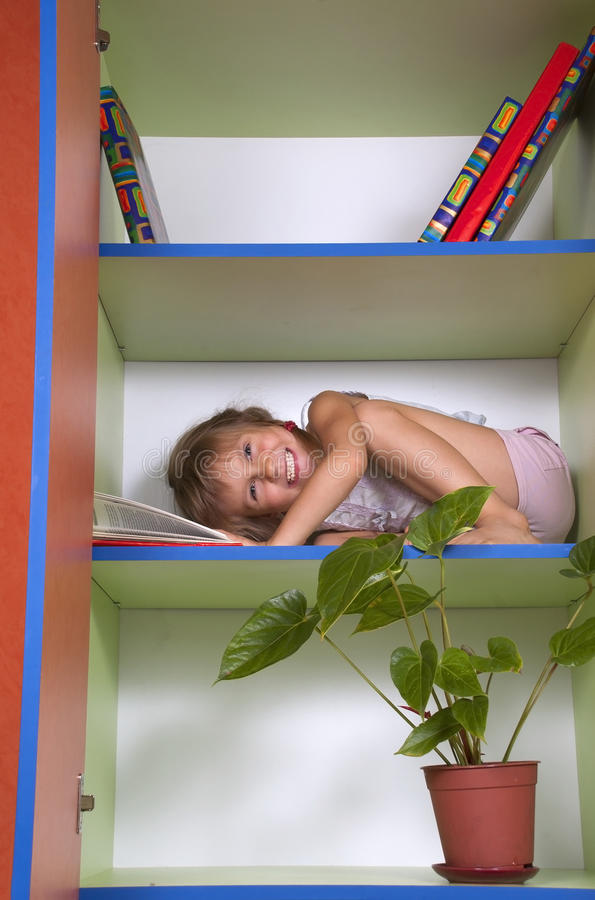 Smiling little girl reading a book in a bookcase. Smiling little girl reading a book on a chelf in a bookcase royalty free stock photography