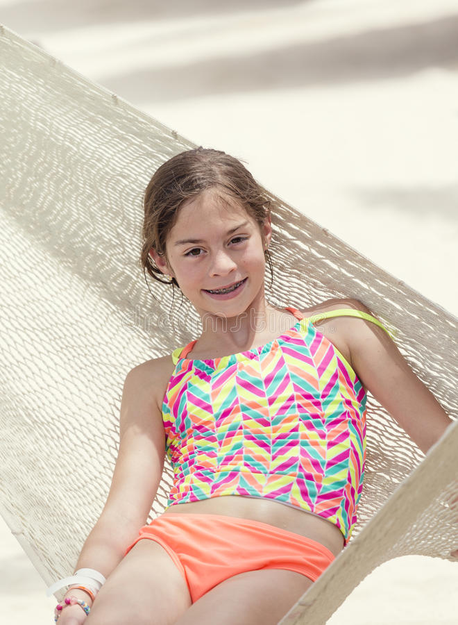 Smiling little girl relaxing in a hammock on vacation. Cute Smiling little girl with braces relaxing in a hammock on a beach vacation royalty free stock images