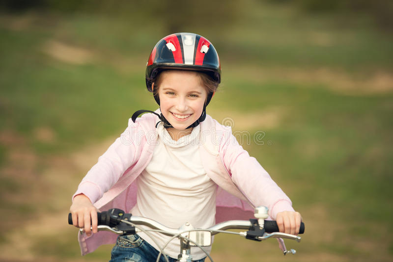 Smiling little girl riding a bike royalty free stock images