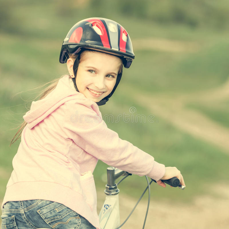Smiling little girl riding a bike turned away stock photos