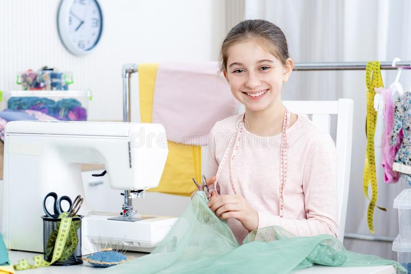 Smiling little girl working at the sewing machine royalty free stock image