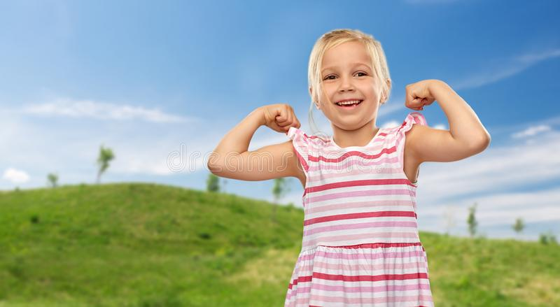 Smiling little girl showing her power in summer royalty free stock photography