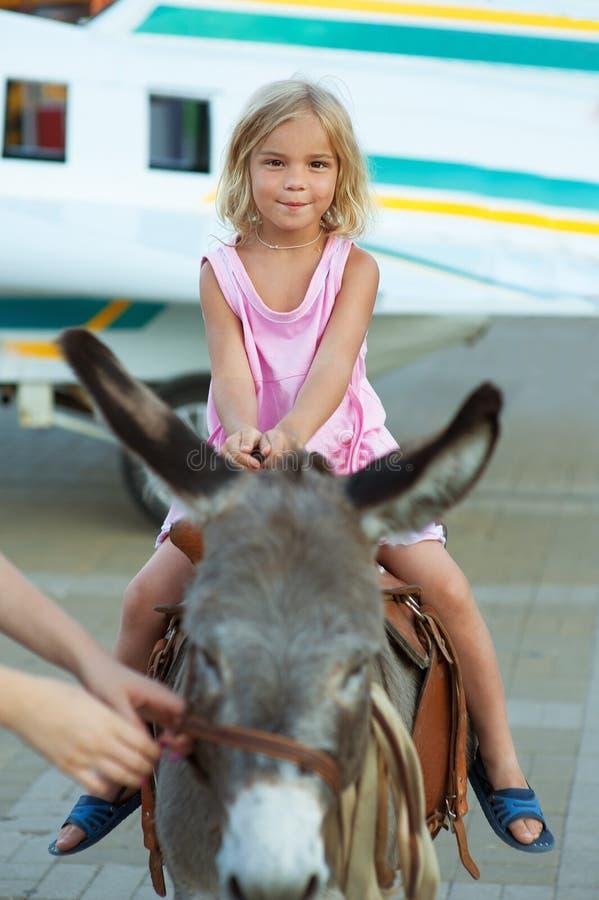 Download Smiling Little Girl Sitting On Stock Photo - Image of cute, horseback: 26913772