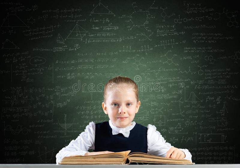 Smiling little girl sitting at desk with open book stock photo