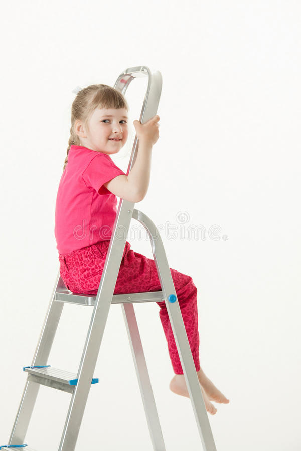 Smiling little girl sitting on the stepladder royalty free stock photo