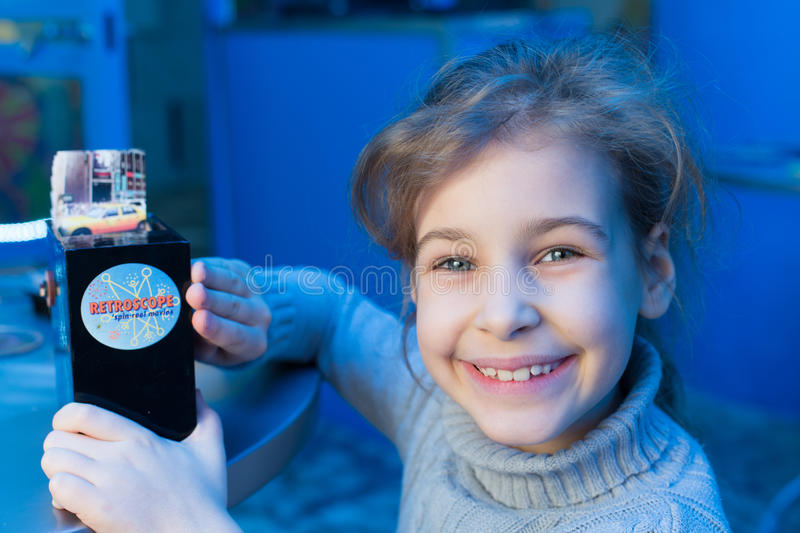 Smiling little girl sitting at a table and holds re. Smiling little girl sitting at a table and holds in her hands retroscope stock photo