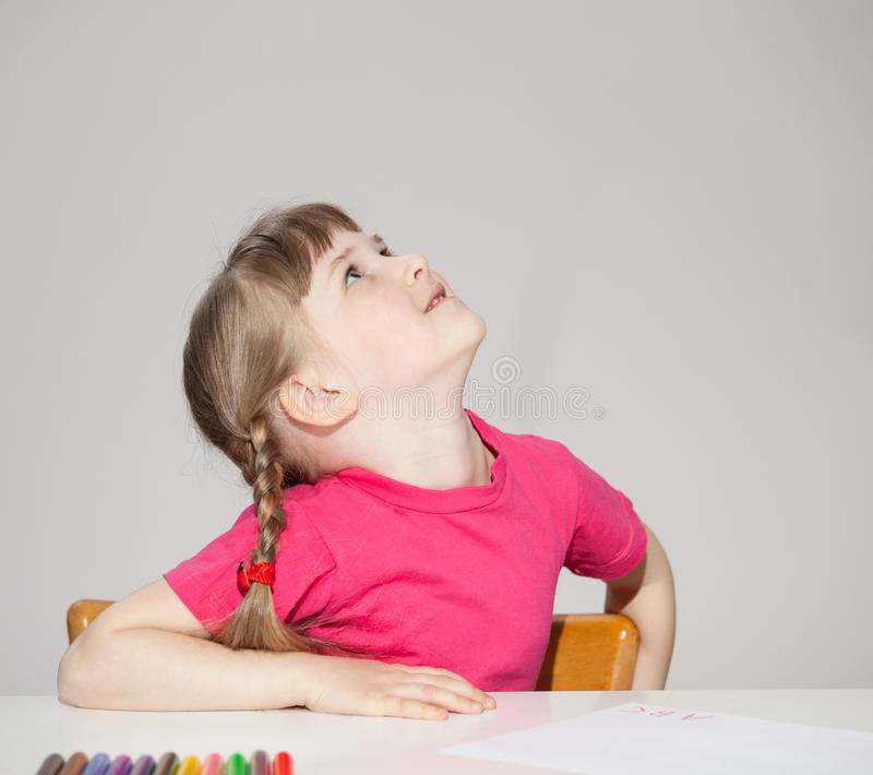 Smiling little girl sitting at the table and looking up stock images