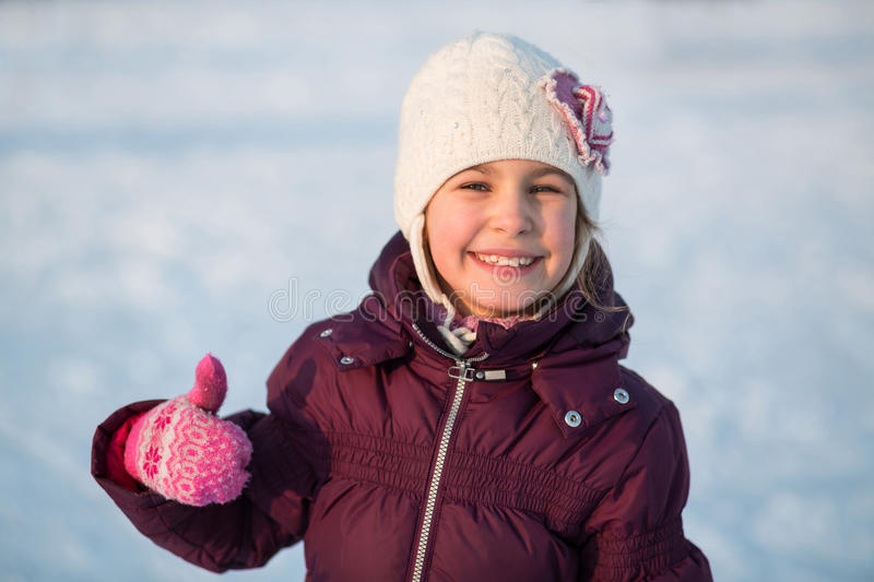Smiling little girl skating at the rink in winter. And showing thumbs up royalty free stock photos