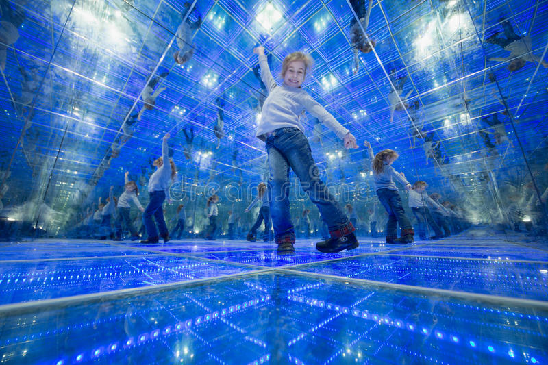 Smiling little girl standing in a mirrored room. And spread her arms out to the side stock photo