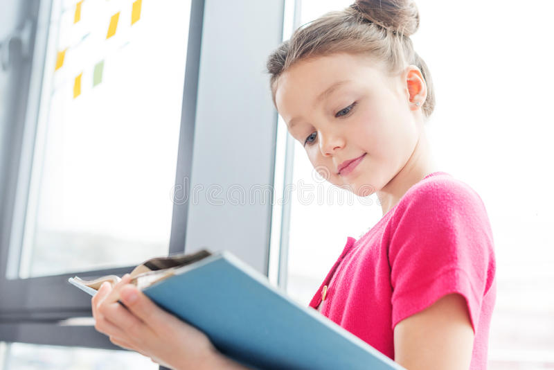 Smiling little girl standing near window and reading book stock photos