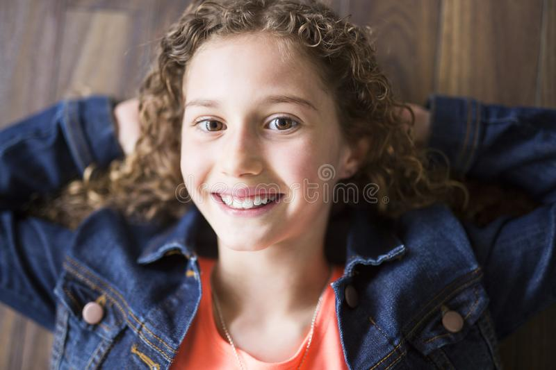 Smiling little girl stretched on a wooden floor with his hands behind his head and looking at camera royalty free stock photo