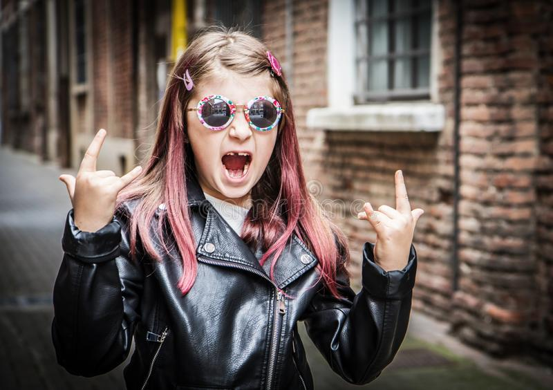 Smiling little girl with sunglasses and leather jacket stock images