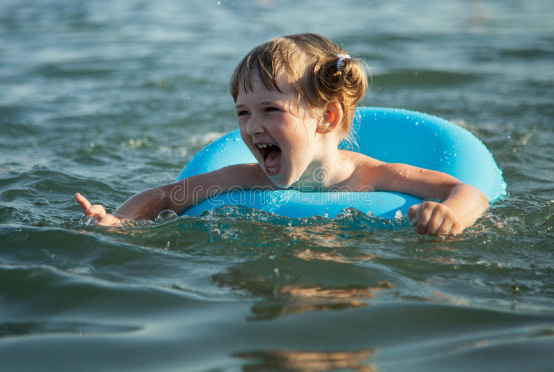 Smiling little girl swimming royalty free stock photography
